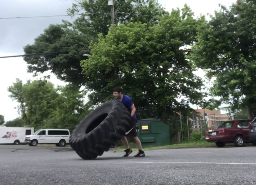 young adult flipping a tire