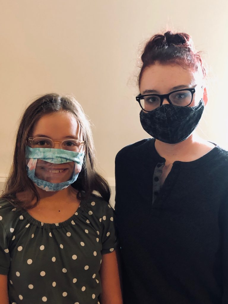 Two young girls, one on the left wearing a see through mask, the one on the right wearing a solid color dark mask.