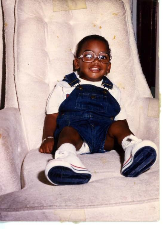LJ a brown-skinned baby with round glasses sitting in a light-colored fabric chair wearing overalls and sneakers.