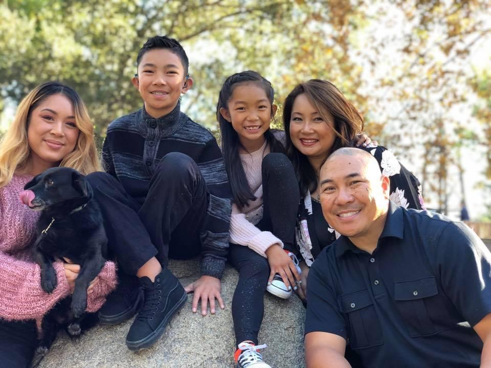 A family of five--girl with shoulder length hair, boy with short dark hair, girl with dark straight hair, woman with dark wavy hair and a bald man.