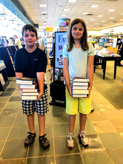 A boy and girl holding a stack of books.