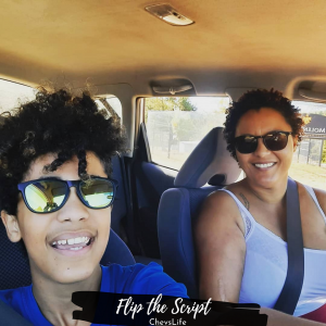 A dark skinned mother with short tight curls, sunglasses,  wearing a sleeveless shirt driving a car with her son. Son is wearing sunglasses and smiling.