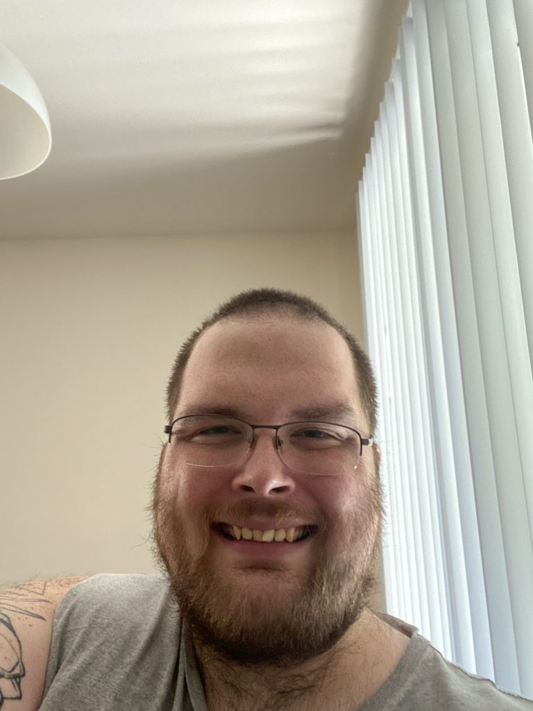 Austin, a bearded young man with wire rimmed glasses smiling.