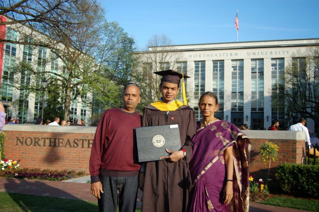 Madhusudhan standing with his parents on either side. His father is on the left wearing a sweatshirt and dark pants. His mother is on the right, wearing a dark sarong with her hair pulled back.