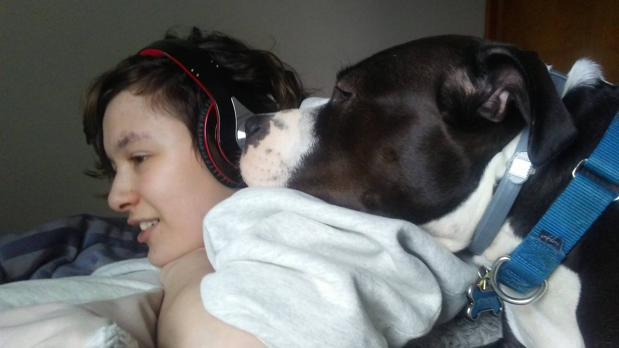 Ari is a light skinned person listening to music with headphones and a dog standing near their shoulder